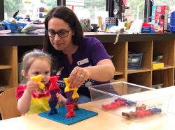 Jessica Malas Wayne YMCA Child Care Director plays blocks with a young child.